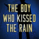 A man standing with a blue background: The Boy Who Kissed the Rain by Shane Wilson